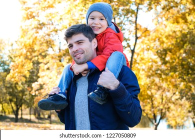 Spending time together outdoors. Father is carrying his son on his shoulders.Autum n season.