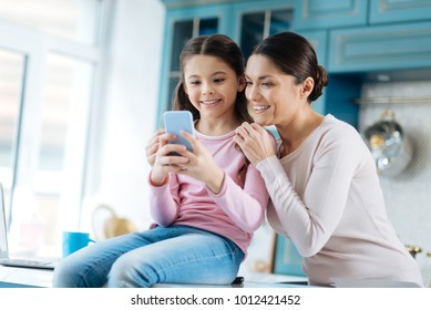 Spending time together. Pretty content dark-haired girl smiling and showing photos on her photos to her mom while mother hugging her