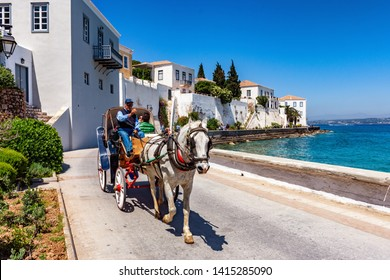 SPETSES, GREECE, 05 MAY 2019 : A young couple enjoys a ride by the seaside, with a horse carriage in Spetses near Athens