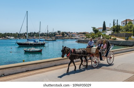 Spetses / Greece - April 28 2018: An unidentified young couple enjoys a ride by the seaside, with a horse carriage. Spetses is a picturesque, small island, where the use of motorcars is not allowed.