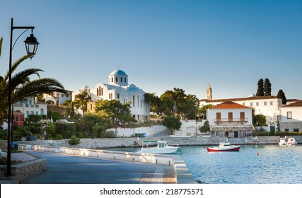 Spetses Town promenade on the Aegean island of Spetses, Greece, showing the old Monastery of Agios Nikolaos which is now the island's cathedral.