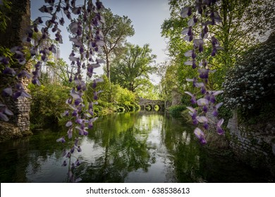 Spettacular bridge in the green water of the river in the Garden ol Ninfa in the province of Latina, Italy, Europe.