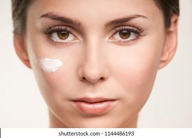 SPF factor cosmetic cream on face. UV care beautiful girl face.
