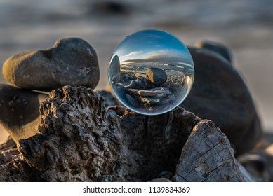 Spherical lens sitting atop driftwood log under the morning light of dawn along this California beach scene.
