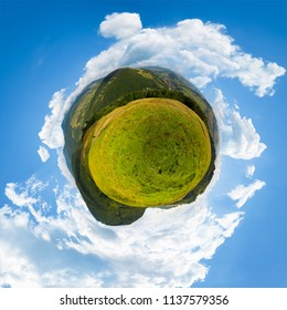 spherical panorama of little mountain planet. lovely countryside concept with 360 degree view. agricultural field on hillside and village in the valley. beautiful sky with fluffy clouds