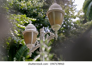 Spherical vintage lantern of two lamps in the garden, hanging iron grate patterned street lamp round shape with white glass, close-up ball-shaped lantern with metal cast elements, garden lightning