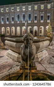 The Sphinx of the Contarini fountain in the foreground in front of the Colleoni library in Piazza Vecchia in Bergamo Alta, historical square of the city of northern Italy, vertical night image