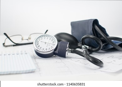 Sphygmomanometer on the working table of a cardiologist. Tonometer, electrocardiogram and notepad for records.