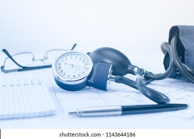 Sphygmomanometer on the working table of a cardiologist. Tonometer, electrocardiogram and notepad with pen for records.
