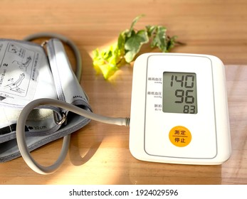 """Sphygmomanometer placed on a wood grain table.The meaning of Japanese is """"Maximum blood pressure, minimum blood pressure, pulse, measurement, stop"""""""