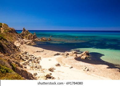 Spiaggia di Rena Maiori beach with azure clear water and mountains, Rena Majore, Sardinia, Italy.
