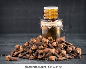 Spice clove essential oil in dark glass bottle and dry cloves on dark wooden background with copy space