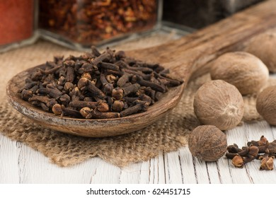 Spice cloves in a wooden spoon on old wooden table.  Selective focus.