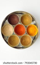 Spice container with turmeric, chilli, coriander, cumin, dry mango, garam masala powders and mustard seeds