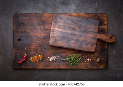 Spice for cooking and empty cutting boards on a dark background. Food background with copyspace. Top view