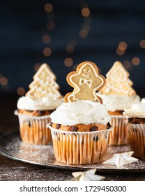 Spice cupcakes with cream cheese frosting decorated with a gingerbread cookies. Selective focus, copy space, close up.