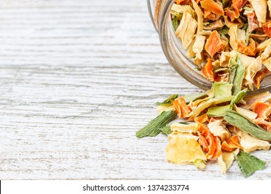 Spice of dried vegetables sprinkled on a wooden table top. Freeze-dried vegetables and free space.