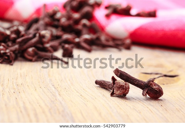 Spice dry cloves heap on kitchen table wooden surface