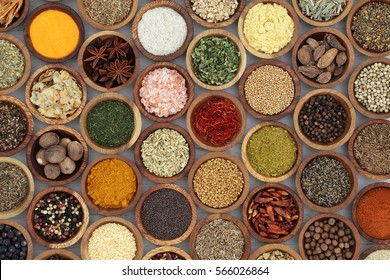 Spice and herb seasoning in wooden bowls forming a background on distressed white wood, high in vitamins and minerals