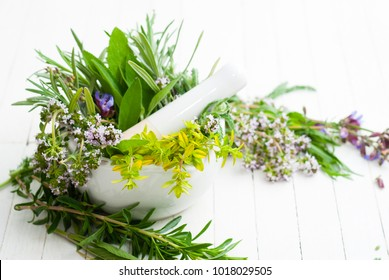 spice and herbal plants in a mortar, white wooden table background
