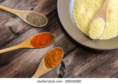 Spice on spoon with bowl of couscous on wood