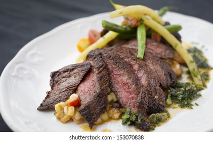 Spice rubbed skirt steak with summer corn succotash, gigante beans, chorizo and scallions