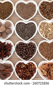Spice selection in heart shaped porcelain dishes over bamboo background.