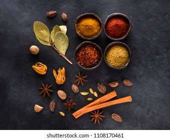 Spice, spicy and seasoning in bowls on a black background