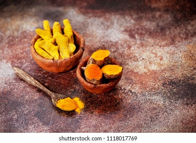 Spice turmeric powder and turmeric root in bowls on a dark concrete background