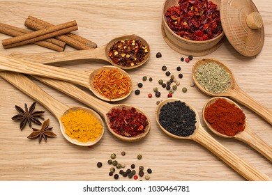 Spice. Spice in a wooden spoon. Herbs. Curry, saffron, turmeric, pepper and others on a wooden background.