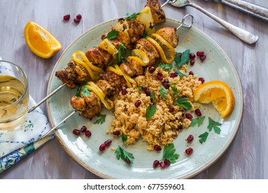Spiced chicken and lemon skewers with couscous garnished with pomegranate seeds and parsley