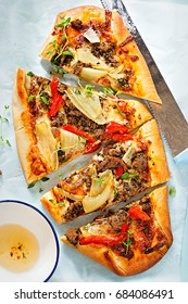 Spiced lamb pide flatbread topped with tomato sauce, lamb, mozzarella, onion, red peppers