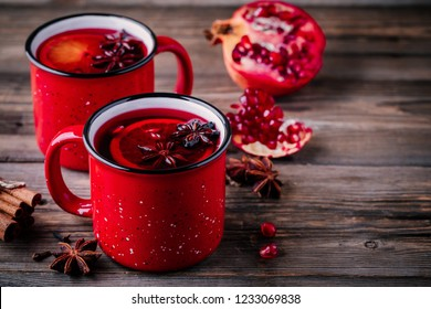 Spiced Pomegranate Apple Cider Mulled Wine Sangria in red mugs on wooden background. Hot drinks for Christmas.
