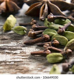 Spices anise stars, cloves and cardamom on the vintage wooden surface