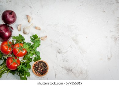 Spices (black pepper, garlic, onion), greens and tomatoes. Ingredients for cooking. On the white stone concrete table top view copy space.