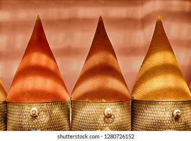 Spices are built into large cones for display in the spice markets in the Marrakesh souk in Morocco. Bands of light come from the ceiling covering.