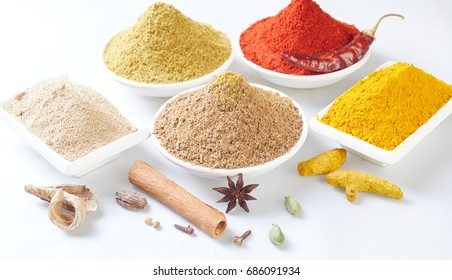 spices in ceramic containers on a wooden background.