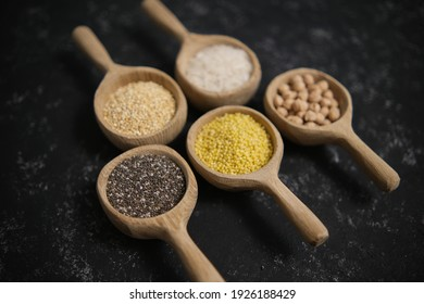 Spices. Chia seeds, millet, rice, chickpeas, quinoa in a wooden spoon on a black and gray background. Five spoons in a row. A set of cereals. Grocery stores. Top view.