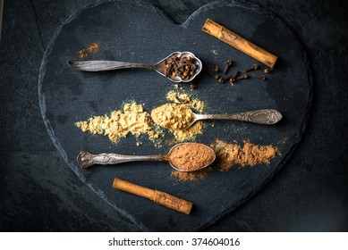 Spices for Christmas Gingerbread Cookies in Spoons on the Dark Grunge Background. Ground Cinnamon, Cinnamon Sticks, Ginger, Cloves, Nutmeg