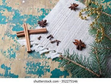 Spices and christmas tree branch on a napkin on old wooden table or board for background. New year theme.