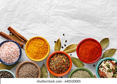 Spices in colorful bowls viewed from above. Various seasonings on a white background. Italian mix, cumin, chili pepper, curry powder, salt, pepper, garlic, cinnamon tomato. Top view. Copy space