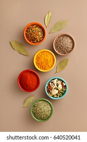 Spices in colorful bowls viewed from above. Various seasonings on a dark background. Italian mix, cumin, chili pepper, curry powder, Himalayan salt, pepper, garlic, cinnamon, dried tomato. Top view
