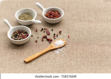 Spices - colorful pepper mix, oregano and pile dried cayenne pepper in the little bowls over textile background