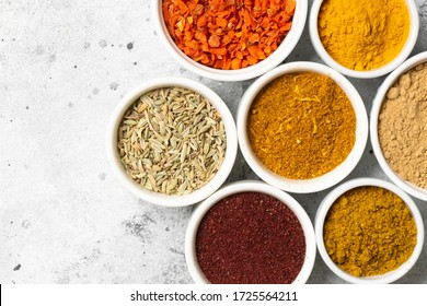 Spices and condiments in white bowls on a light gray table. Turmeric, ginger, curry, fennel and sumac in white bowls. Top view with space for text
