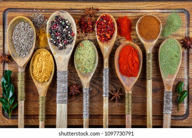 Spices for cooking with kitchen accessories on an old background
