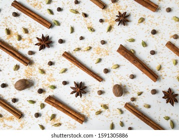 Spices creative  festive  composition with  cinnamon sticks, anise stars, cane sugar, allspice, cardamoms and nutmeg on a white background. Top view