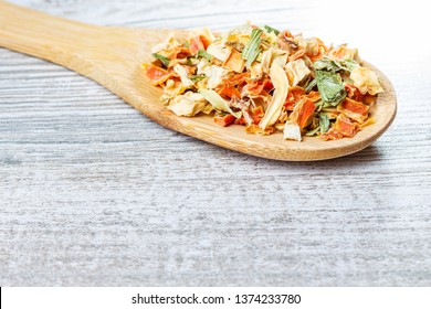 Spices and dried vegetables lying on a wooden spoon. Lyophilized vegetables.
