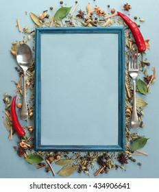 Spices, frame, fork, spoon on black background