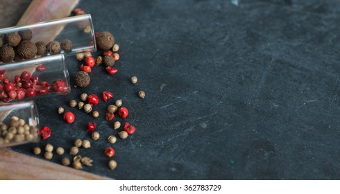 Spices in glass jars on a black board