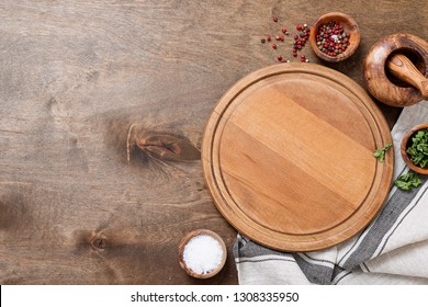 Spices, Herbs, Cutting board for cooking. Round wooden cutting board on wooden  backdrop.